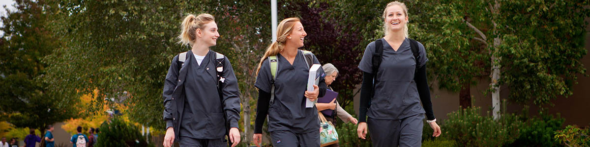 Three female students smiling while walking on campus